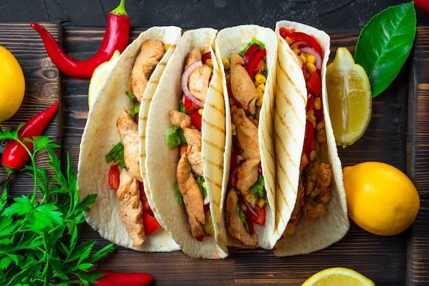 木の板と黒の背景に鶏肉とトウモロコシのラテンアメリカのタコスをクローズアップ
