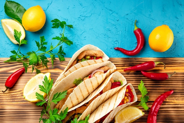 木の板と青い背景に鶏肉とトウモロコシのラテンアメリカのタコスをクローズアップ