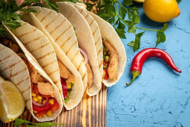 木の板と青い表面に鶏肉とトウモロコシのラテンアメリカのタコスがクローズアップ。