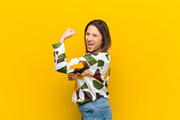 ラテンアメリカ人女性の幸せ、満足、強力な感じ、柔軟なフィット感、上腕二頭筋、黄色の壁に分離されたジムの後に強く見える
