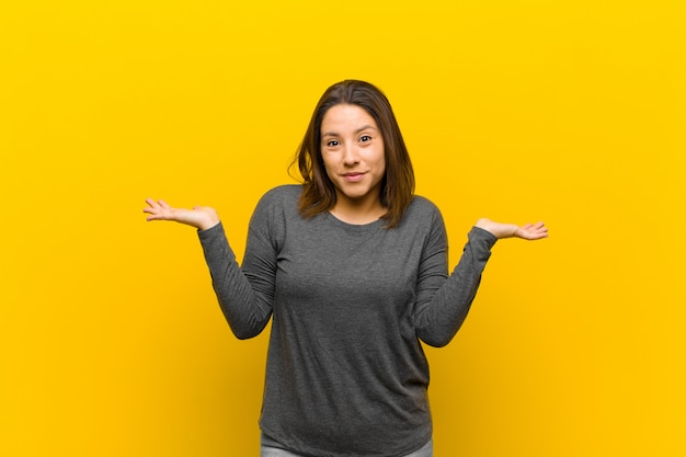 Latin american woman feeling puzzled and confused, doubting, weighting or choosing different options with funny expression isolated against yellow wall
