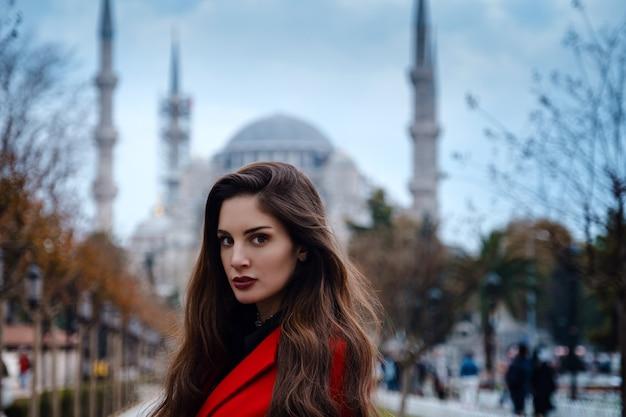 이스탄불의 유명한 블루 모스크 앞에서 세련된 빨간색 코트를 입은 라틴 아메리카 여성 또는 터키 여성, 가을날 모스크 배경에 있는 여행자의 사진.