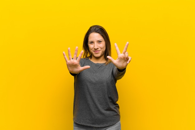 Latin american woman smiling and looking friendly, showing number eight or eighth with hand forward, counting down isolated against yellow wall