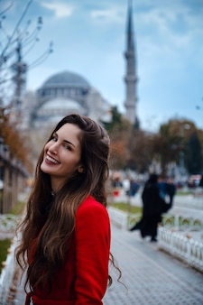 Latin american woman or turkish woman in a red stylish coat in front of the famous blue mosque in istanbul