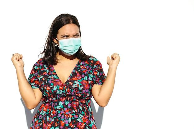 Латинская и естественная молодая женщина в маске на белом фоне. у нее сердитый жест