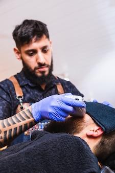 Латинский цирюльник. парикмахер за работой. бородатый и татуированный мужчина работает в парикмахерской. концепция красоты и здоровья.
