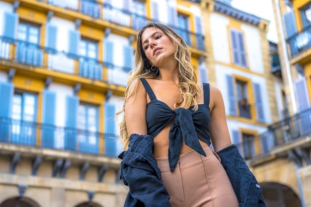 마을 광장에서 포즈를 취하는 라틴계 금발의 여자