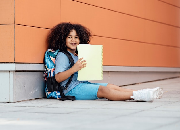 Latin boy with his backpack sitting on the floor looks happily at the camera while holding a notebook