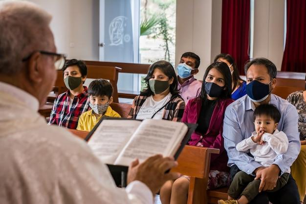 라틴 가족과 함께 전례와 세례를 받는 동안 교회에서 설교하는 라틴 가톨릭 사제