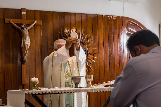 다른 포즈로 전례 중에 교회에서 설교하는 라틴 가톨릭 사제