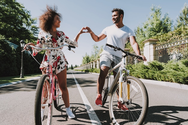 Latin couple go cycling and showing finger heart