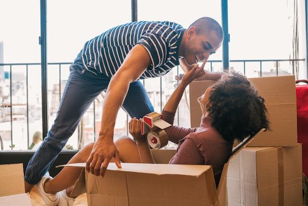Латинская пара весело с картонные коробки в новом доме.