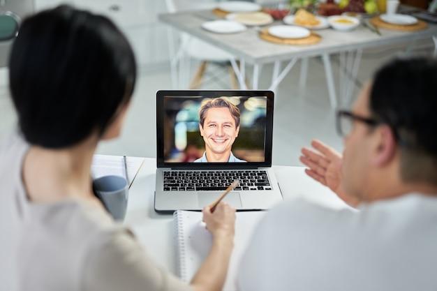 라틴 커플은 노트북을 사용하여 화상 통화를 하는 동안 메모를 하고, 고객에게 연락하고, 웹캠으로 이야기합니다. 온라인 상담 개념입니다. 노트북 화면에 초점