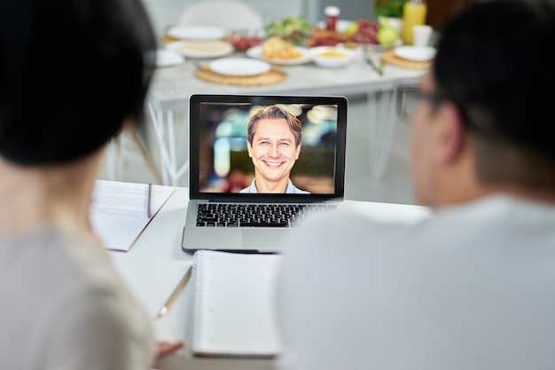 Latin couple making video call to marriage counselor using laptop, looking at screen, talking on webcam. online consultation concept. focus on laptop screen