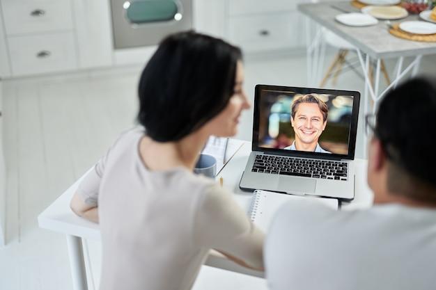 라틴 커플은 노트북을 사용하여 화상 통화를 하고, 회의를 통해 고객에게 연락하고, 웹캠으로 이야기합니다. 온라인 상담 개념입니다. 노트북 화면에 초점