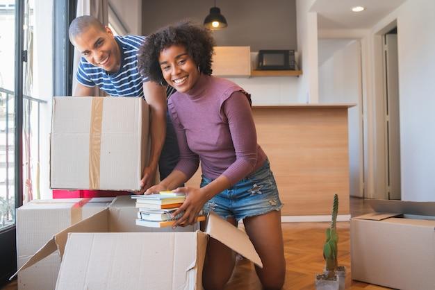 Латинская пара распаковывает вещи в их новом доме.