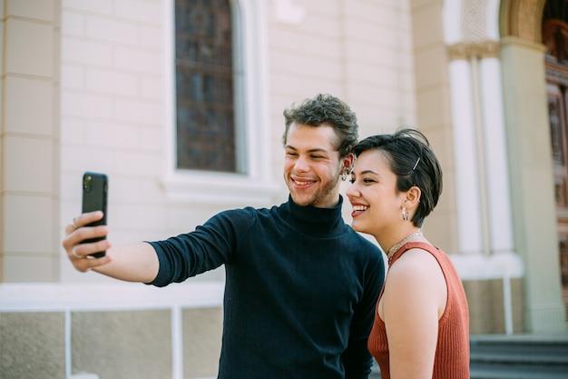 Латинская пара гуляет по городу с помощью смартфона на открытом воздухе.