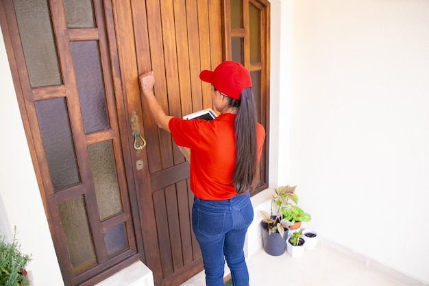 Latin courier knocking on door, holding tablet and carton boxes. brunette long-haired deliverywoman in red uniform standing in front of door and delivering order. delivery service and post concept