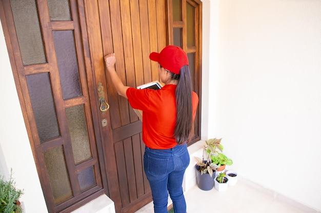 라틴 택배 문을 두드리는, 태블릿 및 판지 상자를 들고. 문 앞에 서서 순서를 전달하는 빨간 유니폼에 갈색 머리 장발 배달원. 배달 서비스 및 포스트 개념