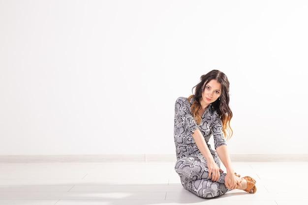 Латинский танец, леди бачата, джаз-модерн и концепция модного танца - красивая молодая женщина-танцор сидит на белом фоне с копией пространства