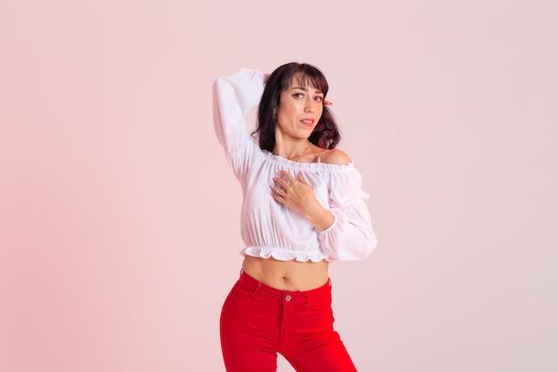 라틴 댄스, 바차타 레이디, 재즈 모던, 보그 댄스 개념 - 카피 공간이 있는 배경에서 춤을 추는 아름다운 젊은 여성