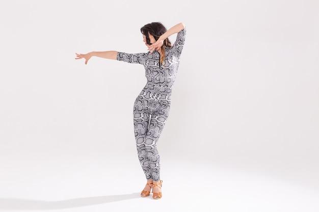 Латинский танец, леди бачата, джаз модерн и концепция модного танца - красивая молодая женщина танцует на белом фоне с копией пространства