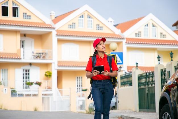Donna di consegna latina che cerca indirizzo e che tiene compressa. giovane corriere femminile che consegna l'ordine nello zaino termico giallo.