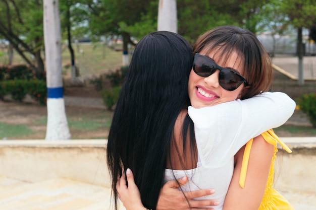 公園に立って一緒に抱きしめるラテン女性の友人。