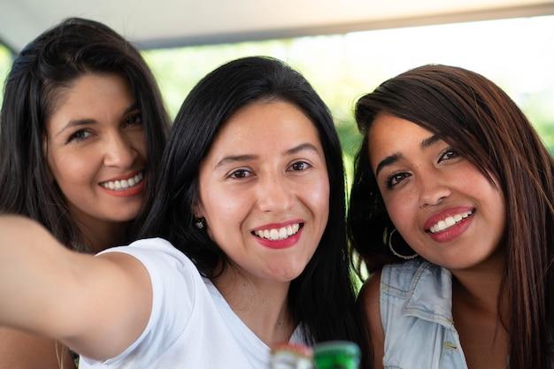 ソーシャルネットワークで自分撮りをしているラテン系の友人3人の若いヒスパニック系の友人が写真を撮っている