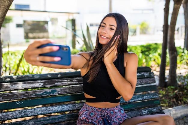 Ragazza latina che ottiene un selfie su una panca di legno nel parco