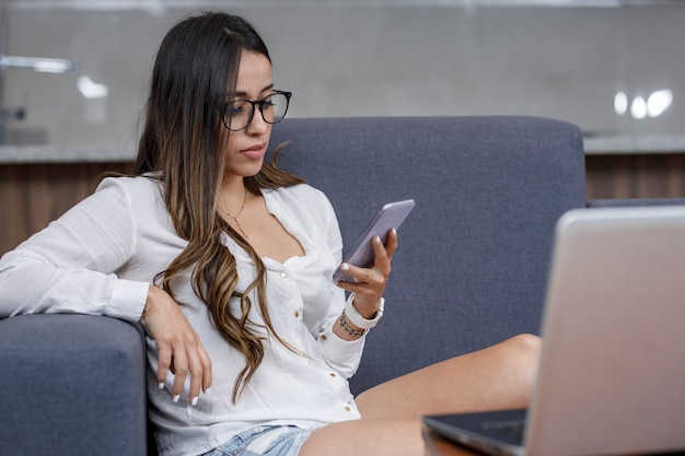 ノートパソコンを持って居間で作業中に携帯電話でメッセージを送信するラテン系の女の子