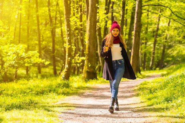 Латинская девушка с черной курткой, шарфом и красной шерстяной шляпой наслаждается осенним парком, гуляя по дорожке с кофе на закате