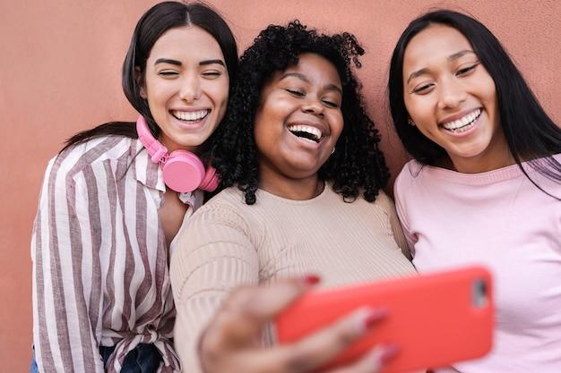 Латинские девушки веселятся вместе в городе, делая селфи с мобильным телефоном - концепция дружбы и счастья - основное внимание уделяется лицу молодой женщины в центре