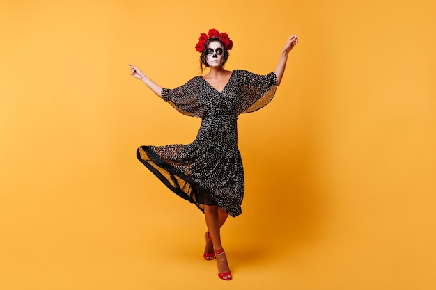 Latin lady emotionally dances in her magnificent outfit. full-length shot  of model with halloween makeup