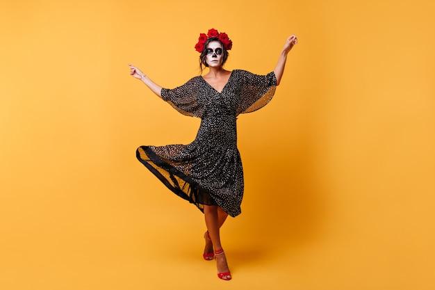 라틴 여성은 멋진 의상을 입고 감정적으로 춤을 추고 있습니다. 할로윈 메이크업을 한 모델의 전체 길이 샷