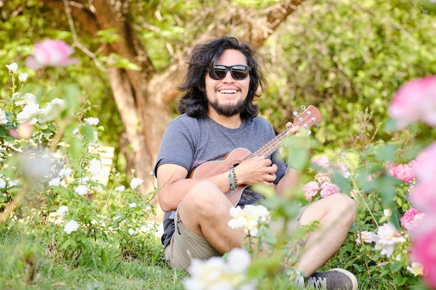 Latin man alone playing the ukulele sitting in the middle of a meadow full of flowers, on a sunny spring day.