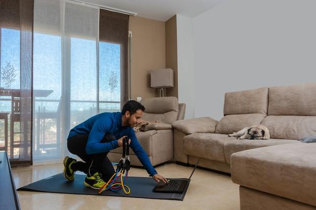 Латиноамериканец тренируется в гостиной с резинкой во время онлайн-занятий