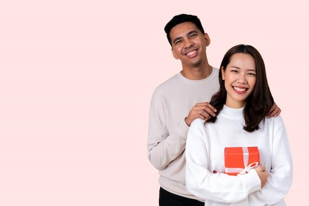 ラテン男はバレンタインデーのためのピンクの背景に分離された幸福笑顔でアジアの女性を受け入れる