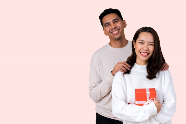 Latin man embrace asian woman with happiness smile isolated on pink background for valentine day