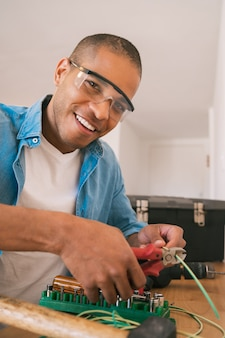 Latin man fixing electricity problem at home.