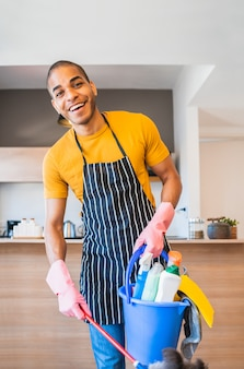 Latin man holding a bucket with cleaning items.