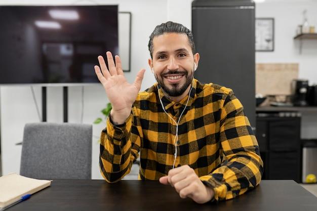 ビデオ通話で話しているオフィスで格子縞のシャツを着たラテン系男性
