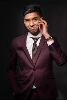 カメラを見て電話で話している黒い背景の上のスーツを着たラテン人
