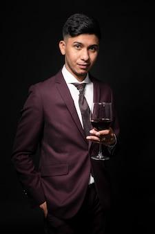 手にワインのガラスと黒の背景にスーツのラテン男