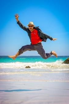 幸せな美しいビーチにジャンプラテン男