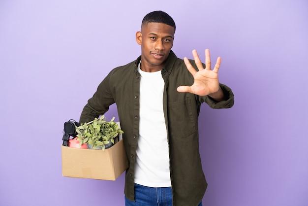 Латинский мужчина делает движение, поднимая коробку, полную вещей, считая пять пальцами