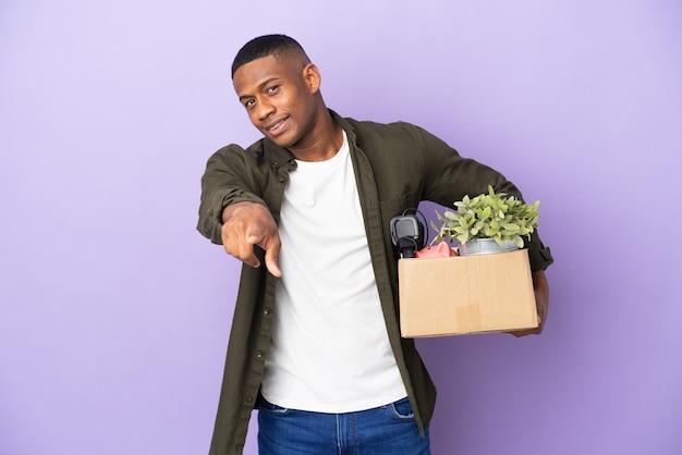 Латинский мужчина делает движение, поднимая коробку, полную вещей, указывая вперед со счастливым выражением лица