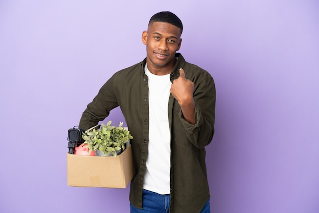 Latin man making a move while picking up a box full of things doing coming gesture