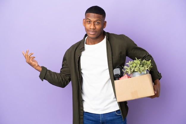 Latin man making a move while picking up a box full of things extending hands to the side for inviting to come