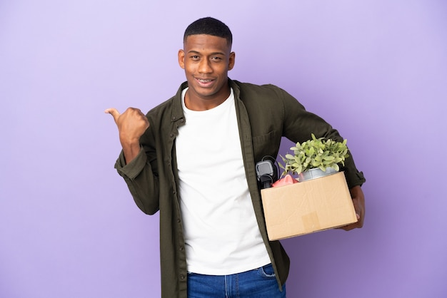 Latin man making a move while picking up a box full of things pointing to the side to present a product
